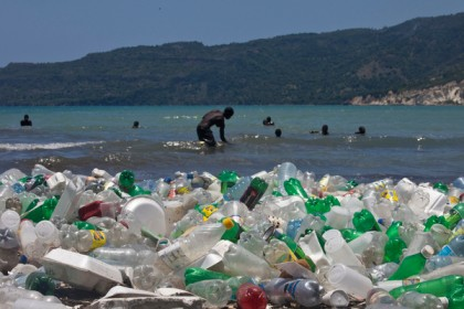 Children play on the litter-strewn beach off Jacmel